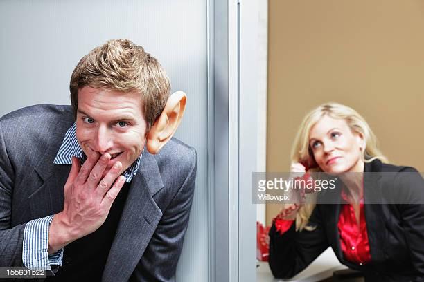 Homme Écouter d'une oreille indiscrète à l'extérieur du bureau