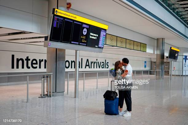 Man embraces a newly arrived passenger at Heathrow airport, west London, on May 22, 2020. - Travellers arriving in Britain will face 14 days in...