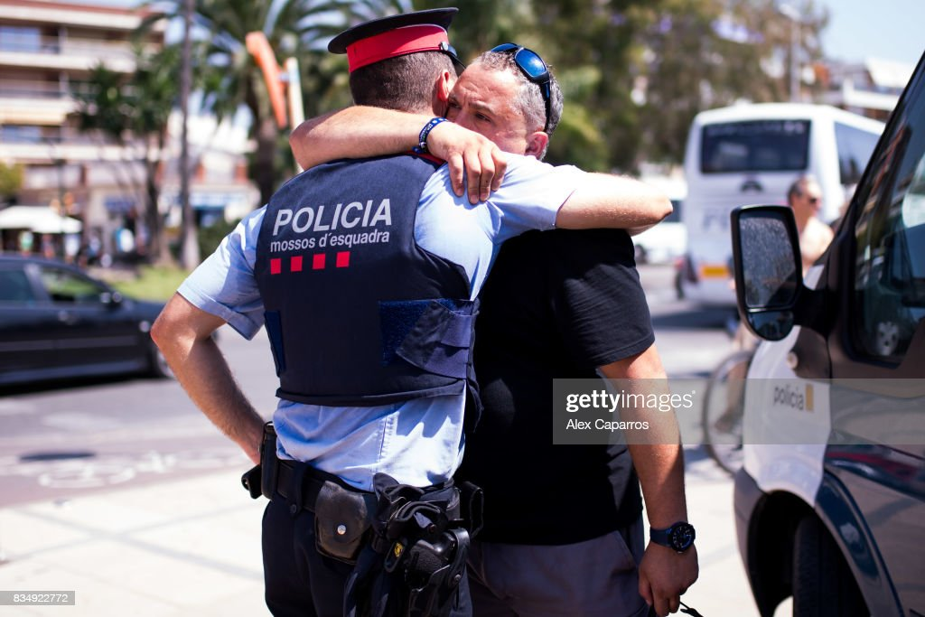 A man embraces a police officer on the spot where five terrorists were shot by police on August 18, 2017 in Cambrils, Spain. Fourteen people were killed and dozens injured when a van hit crowds in the Las Ramblas area of Barcelona on Thursday. Spanish police have also killed five suspected terrorists in the town of Cambrils to stop a second terrorist attack.