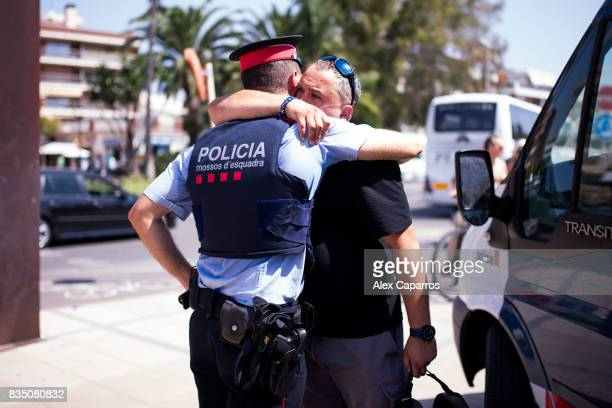 A man embraces a police officer on the spot where five terrorists were shot by police on August 18 2017 in Cambrils Spain Fourteen people were killed...