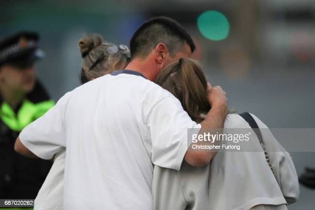 A man embraces a woman and a teenager as he collects them from the Park Inn Hotel where they were given refuge after last nights explosion at the...