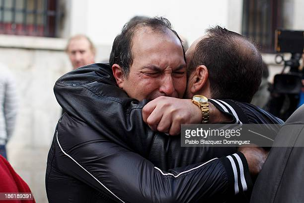 Man embraces another mourner after a six-minute silence was observed by other miners and family members of the six coal miners killed by a gas leak...