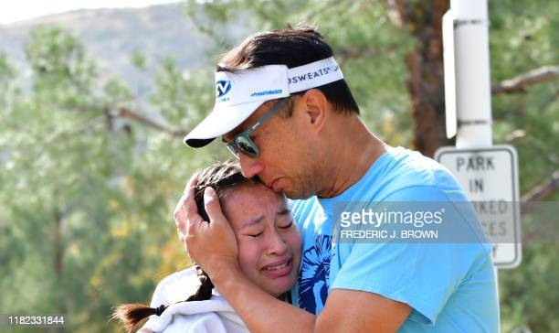 A man embraces his daughter after picking her up at Central Park after a shooting at Saugus High School in Santa Clarita California on November 14...