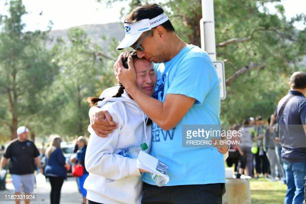 TOPSHOT A man embraces his daughter after picking her up at Central Park after a shooting at Saugus High School in Santa Clarita California on...