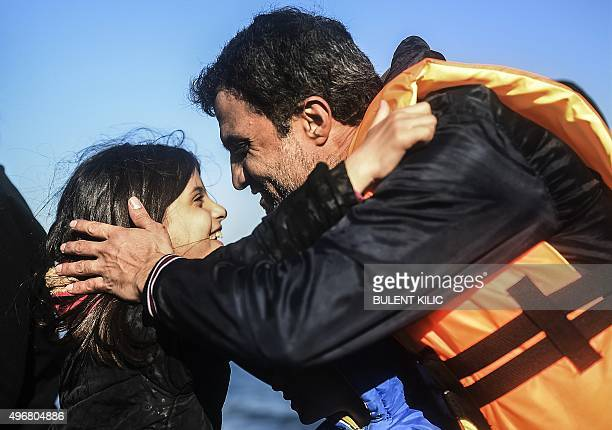 A man embraces his daughter upon reaching the shore as refugees and migrants arrive to the Greek island of Lesbos after crossing the Aegean Sea from...