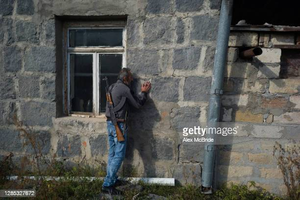 Man embraces the walls of his home before abandoning it as fear of Azeri persecution prompts him to leave his homeland on November 12, 2020 in...