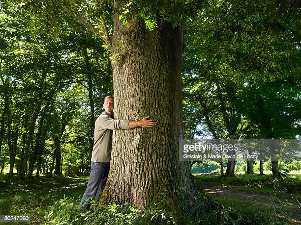man embracing a tree trunk. - tree hugging stock pictures, royalty-free photos & images