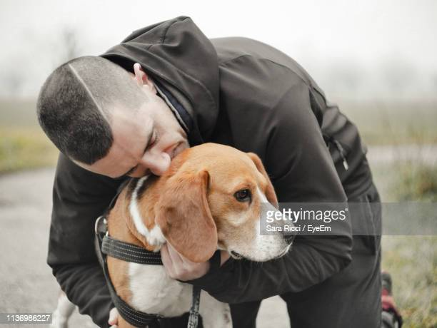 man embracing dog - beagle stock pictures, royalty-free photos & images