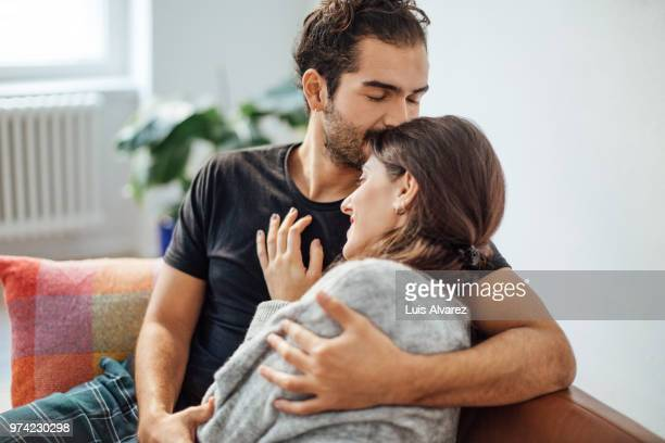 man embracing girlfriend while kissing on her forehead at home - embracing stock pictures, royalty-free photos & images