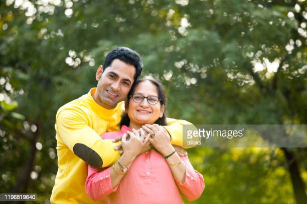man embracing mother at park - son stock pictures, royalty-free photos & images