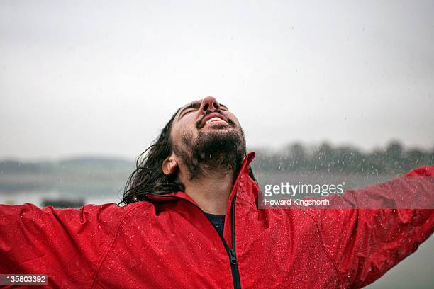 man embracing the weather with arms extended