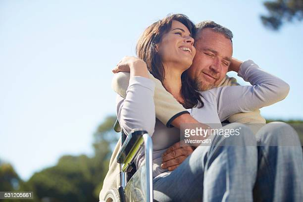 Man embracing woman in wheelchair