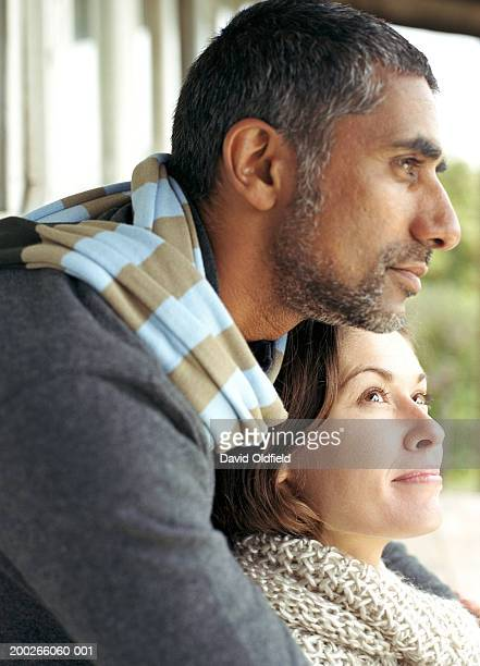 Man embracing woman outdoors, close-up, side view