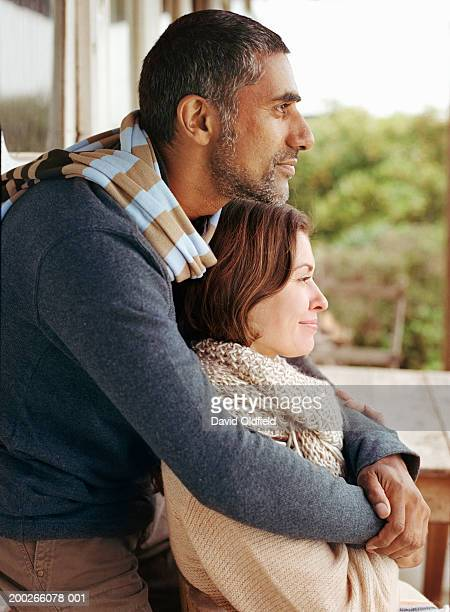 Man embracing woman outdoors, side view