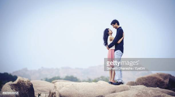 Man Embracing Woman While Standing On Rock Against Sky