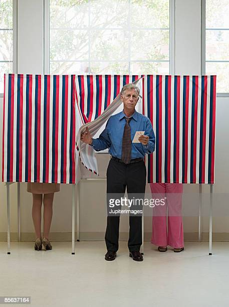 Man emerging from voting booth