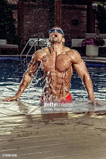 Man emerging out of pool wearing goggles