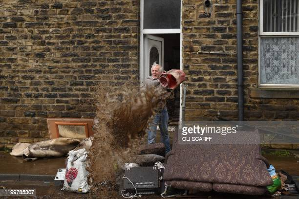 TOPSHOT A man empties a bucket of water over debris outside a house in Mytholmroyd northern England on February 10 2020 after flooding brought by...