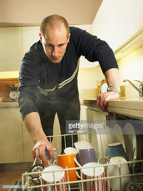 Man emptying dishwasher, leaning on kitchen worktop