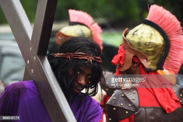 A man enacting Jesus Christ carries a cross after receiving a beating during a procession to mark Good Friday in Lagos on April 14 2017 Thousands of...