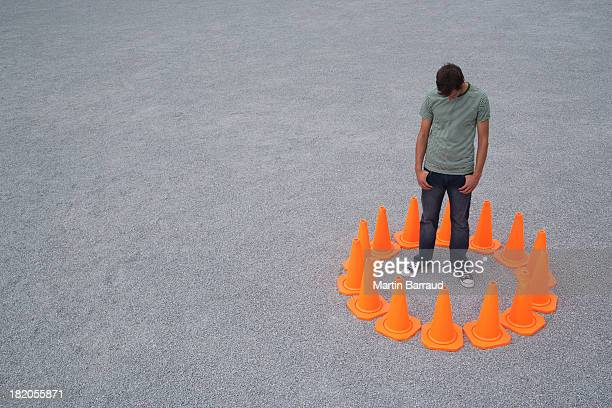 Man encircled by safety cones