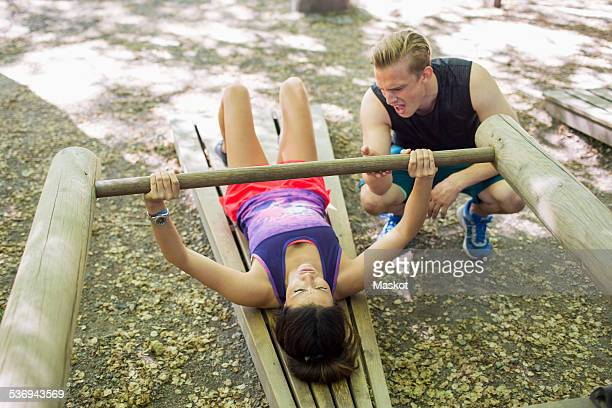 Man encouraging woman in lifting wooden weight at outdoor gym