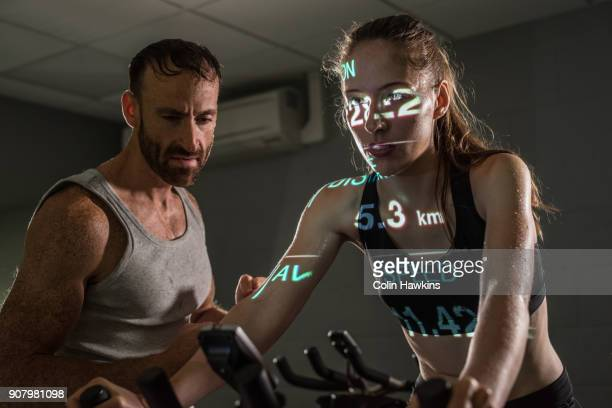 Man encouraging woman on exercise bike with infographic