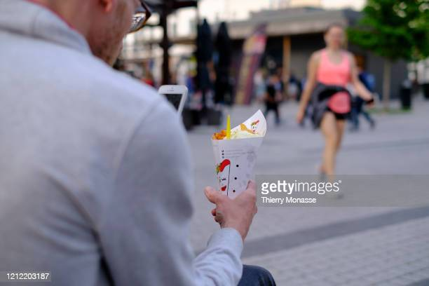 A man enjoy French fries from Maison Antoine on 'Place Jourdan' on May 8 2020 in Brussels Belgium In order to contain the spread of the severe acute...