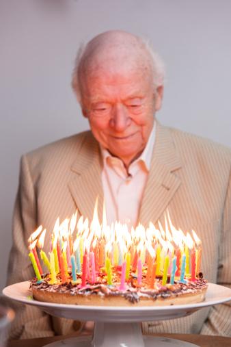 Man enjoying 93 candles on a birthday cake - gettyimageskorea