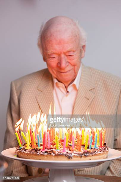 Man enjoying 93 candles on a birthday cake
