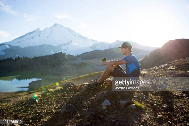 a man enjoying a morning cup of coffee while on a backpacking trip near mt. baker. - bellingham stock pictures, royalty-free photos & images