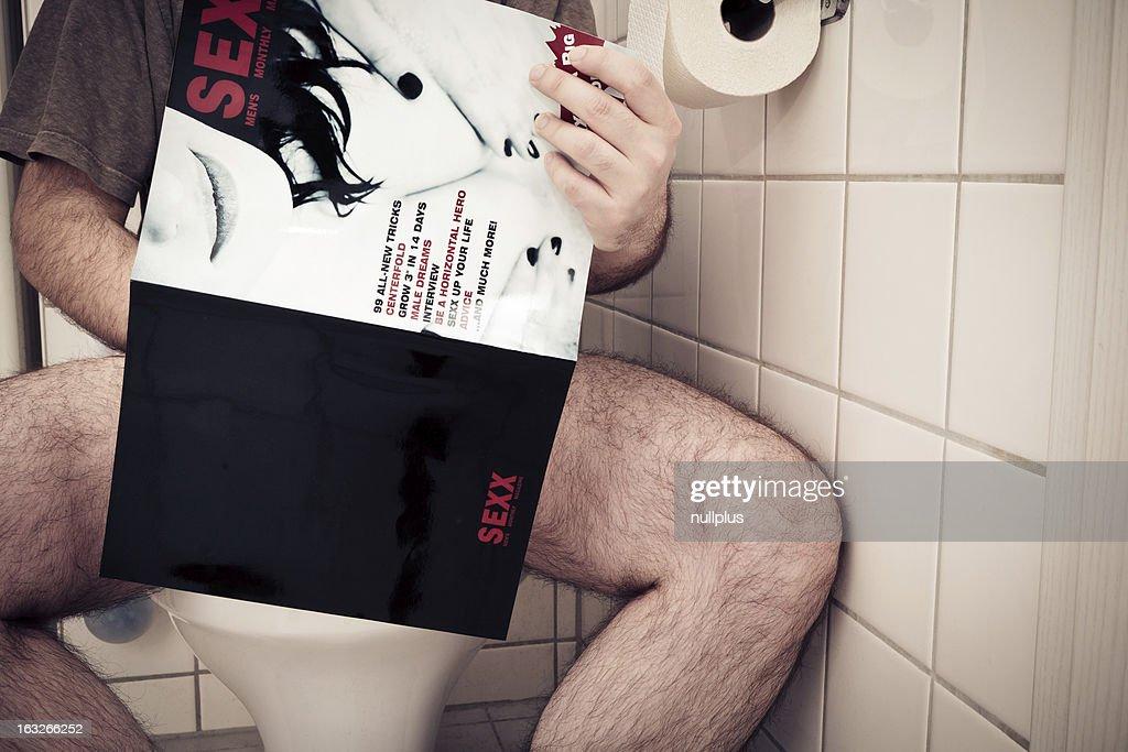 man enjoying a porn magazine : Stock Photo