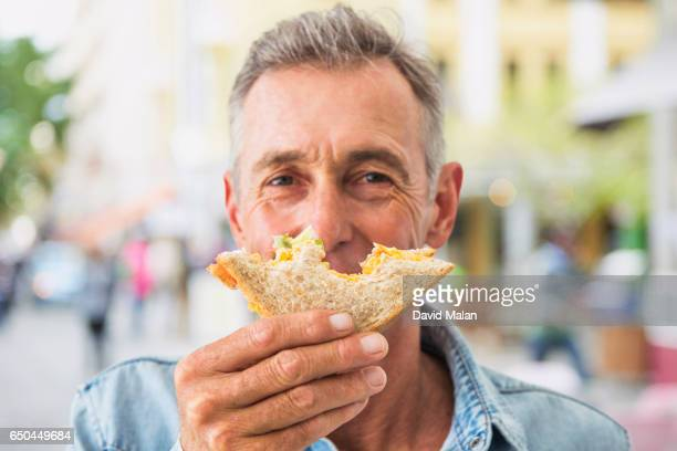 Man enjoying a sandwich outdoors.