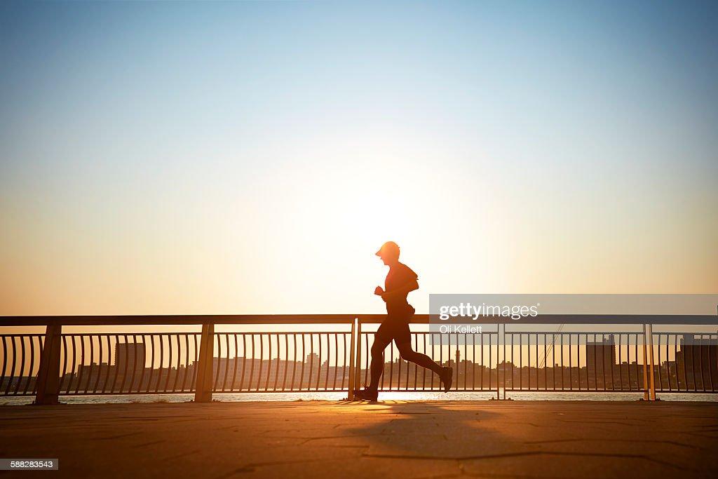 Man enjoying an early morning jog in the city. : Stock Photo