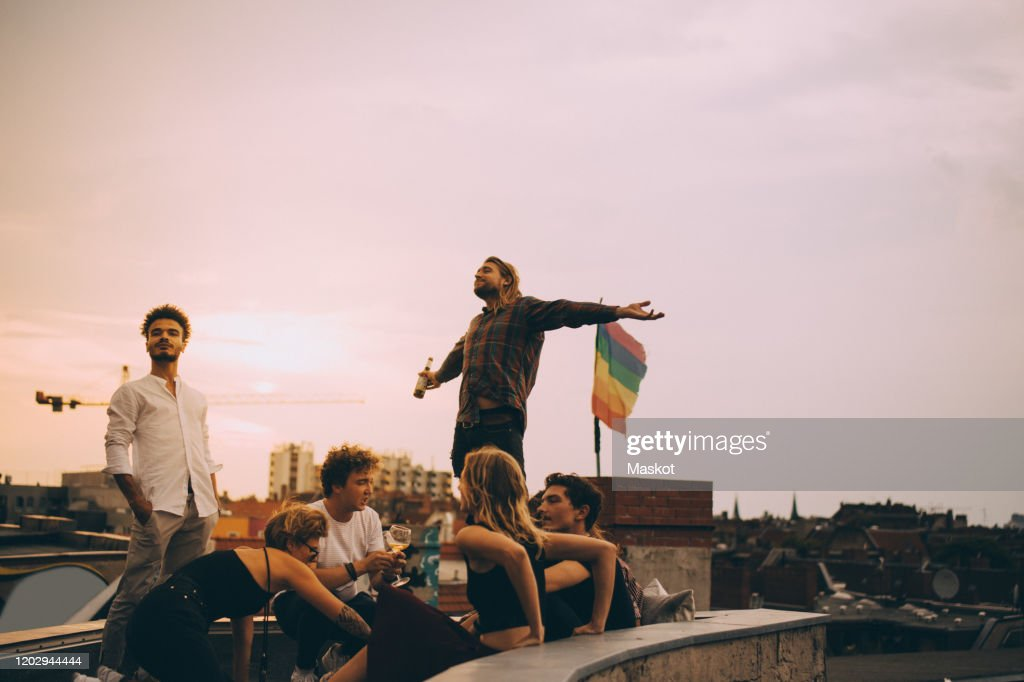 Man enjoying beer while relaxing with friends on terrace at rooftop party : Stock-Foto