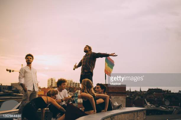 man enjoying beer while relaxing with friends on terrace at rooftop party - freundschaft stock-fotos und bilder