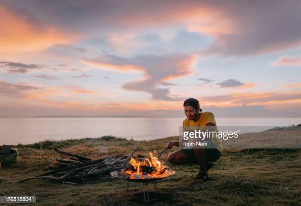 man enjoying campfire at seaside campsite at sunset - キャンプ 1人 ストックフォトと画像