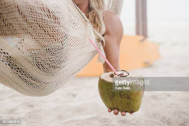 man enjoying coconut water in hammock on beach - coconut water stock pictures, royalty-free photos & images