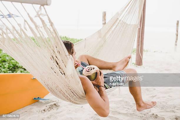 Man enjoying coconut water in hammock on beach