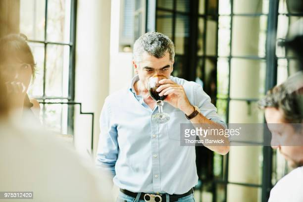 Man enjoying drink during dinner party with family