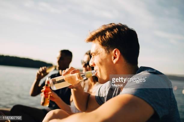 man enjoying drink with friends while sitting on jetty against sky in summer - bootssteg stock-fotos und bilder