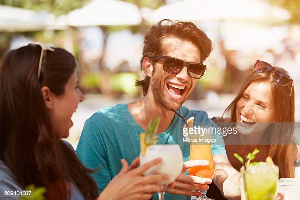 Man enjoying drinks with friends at restaurant