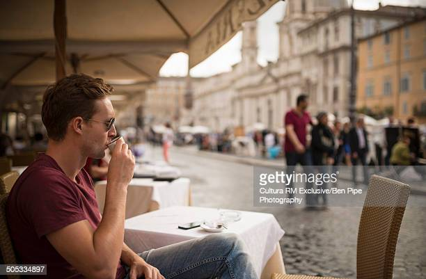 Man enjoying espresso at restaurant, Piazza Navona, Rome, Italy