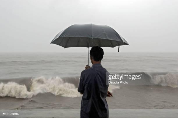 Man enjoying hightide waves at Worli, Bombay, Mumbai, Maharashtra, India