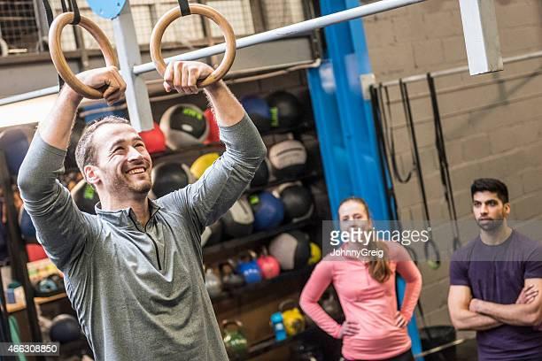Man enjoying his workout using rings at gym