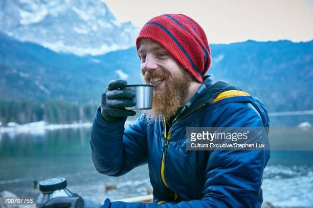 Man enjoying hot drink by Eibsee Lake at base of Zugspitze, Garmisch-Partenkirchen, Bavaria, Germany