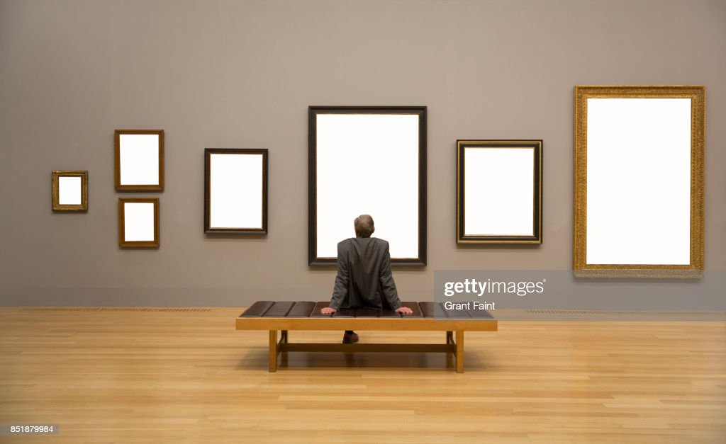 Man Enjoying Looking At Blank Frames On Wall Stock Photo | Getty Images