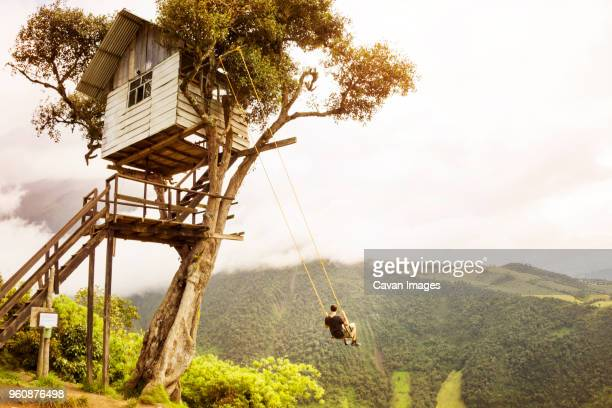 man enjoying on swing against mountain and sky - tree house stock pictures, royalty-free photos & images