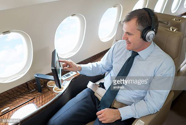 Man enjoying onboard entertainment while traveling in first class