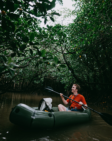 Man enjoying paddling inflatable raft in mangrove jungle, Okinawa, Japan - gettyimageskorea